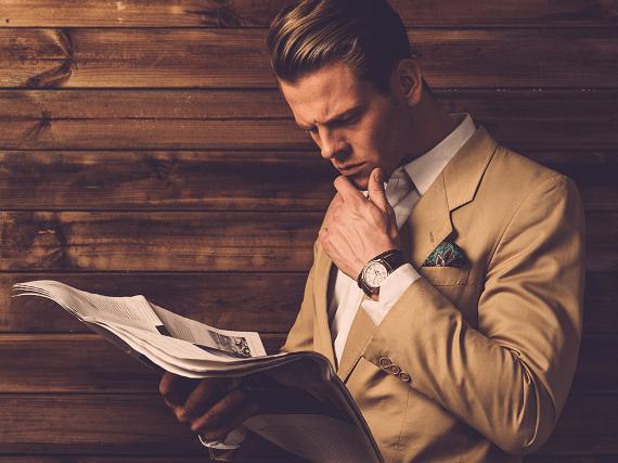 Elegantne oblečený muž s novinami v ruke