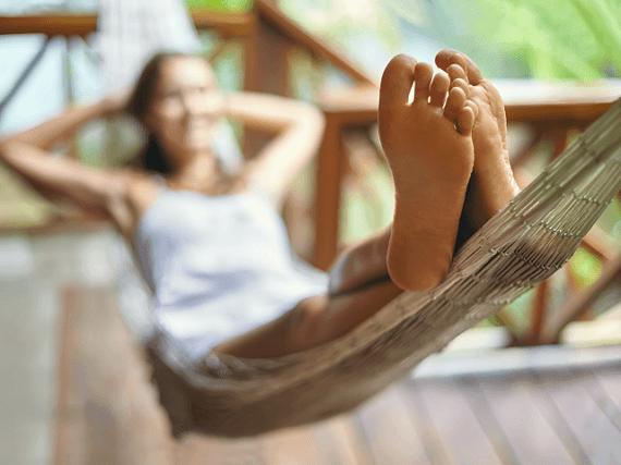 Žena leží v sieťovanej posteli a relaxuje